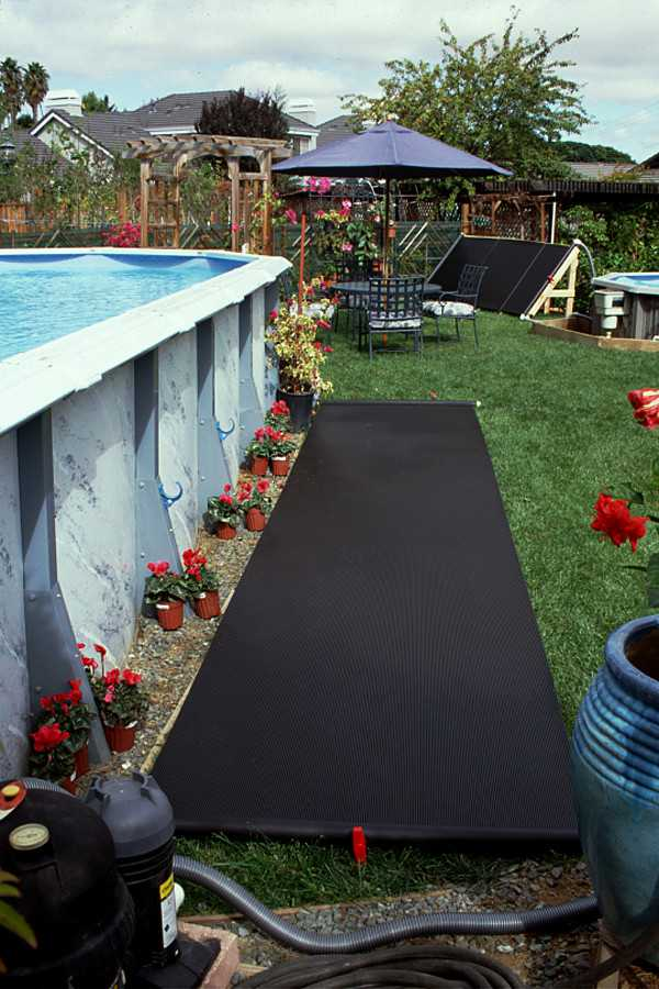Example of how a Solar Bear above ground pool heater can be installed. The black solar bear solar collector is shown rolled out next to an oval above ground swimming pool.
